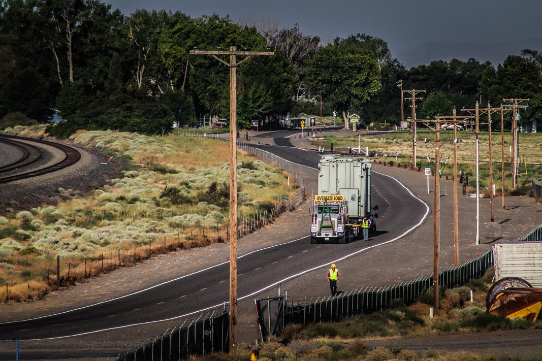 Omega Morgan specialized transportation crew member stands on the side of the road to assist while a heavy transformer load comes up a winding road in Oregon state